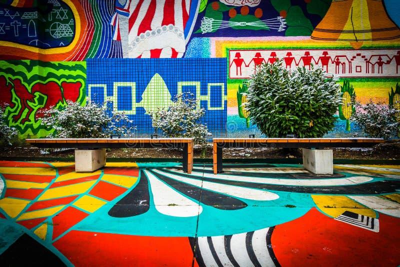 Bänkar och färgrik väggmålning i norr Charles, Baltimore, Maryland arkivfoto