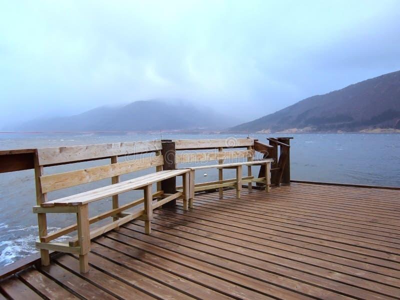 Bänkar på pir på fjorden i Norge arkivbild