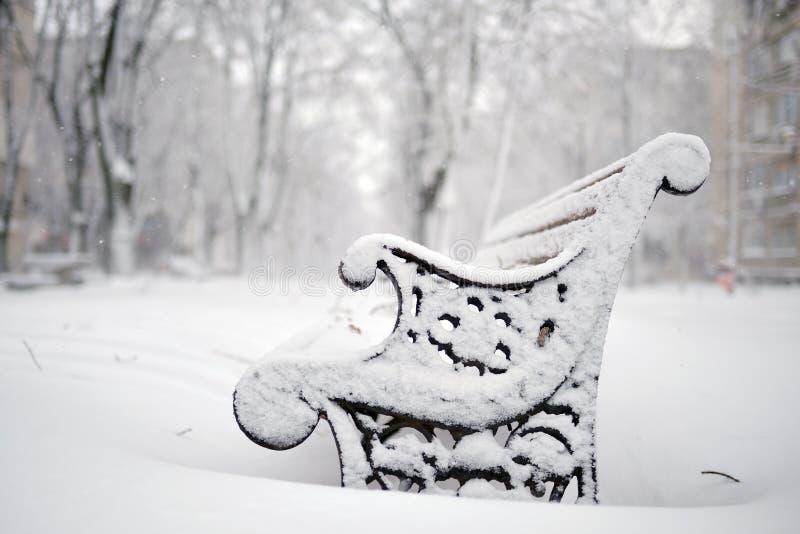 Bänkar som täckas med insnöad vinter arkivfoto
