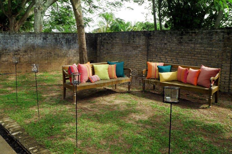 Bänke mit Kissen im Garten stockfoto