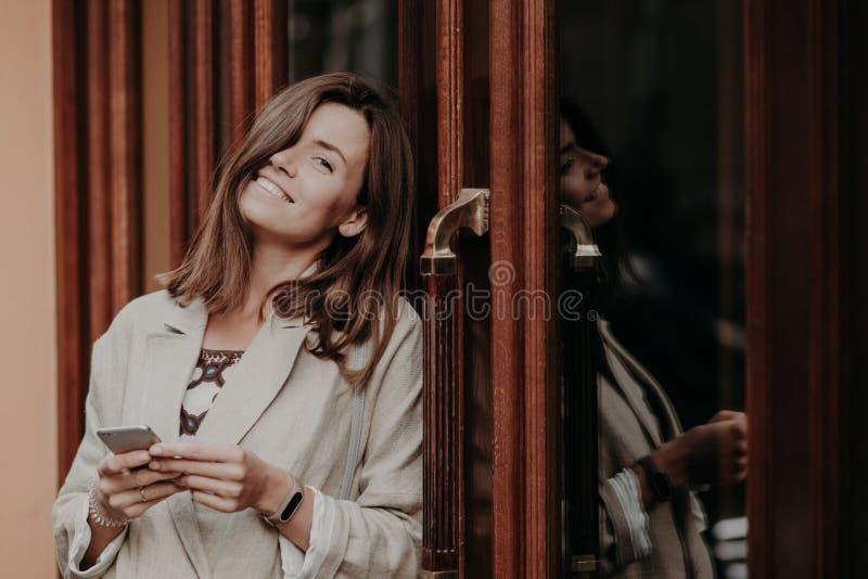 Bär den unga kvinnan för den positiva brunetten med toothy leende, smartwatch, det iklädda eleganta omslaget, den moderna mobilte arkivfoto