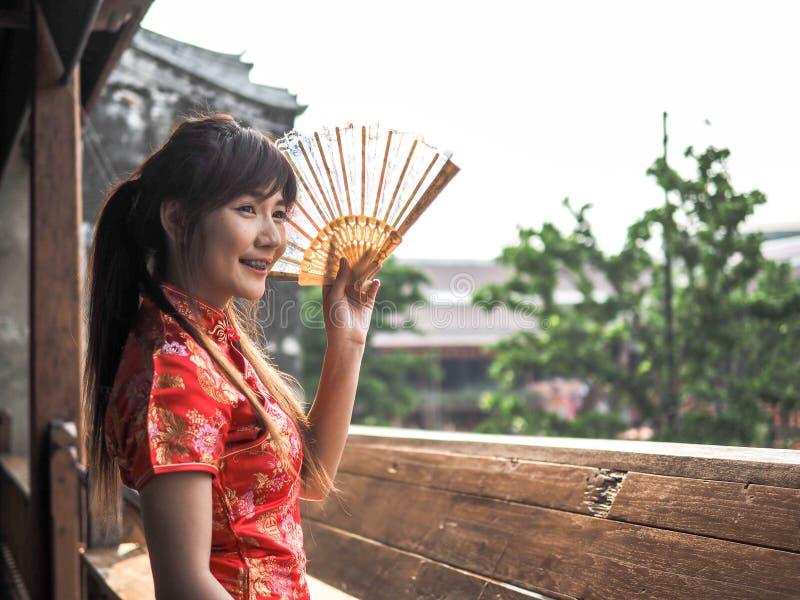 Bär det härliga asiatiska kvinnaleendet för ståenden den traditionella kinesiska klänningen som rymmer en fan fotografering för bildbyråer