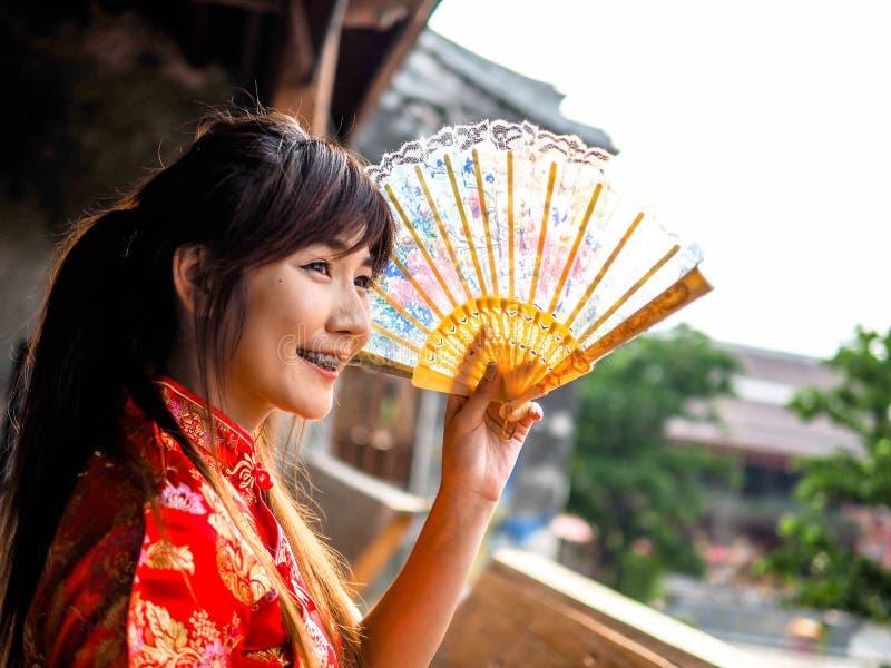 Bär det härliga asiatiska kvinnaleendet för ståenden den traditionella kinesiska klänningen som rymmer en fan som ser yttersidan  royaltyfria foton