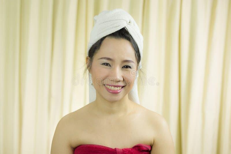 Bär det tillförordnade leendet för kvinnan, ledset som är roligt, en kjol för att täcka hennes bröst efter tvättar hår s royaltyfria bilder