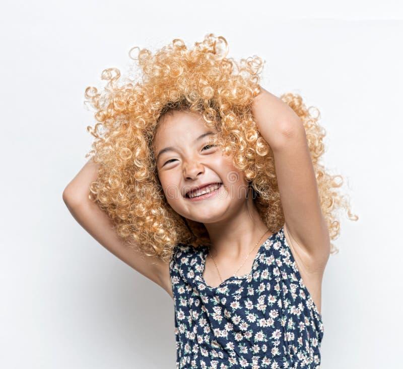 Bära en blond peruk och en rolig ansiktsuttryckasiatflicka fotografering för bildbyråer