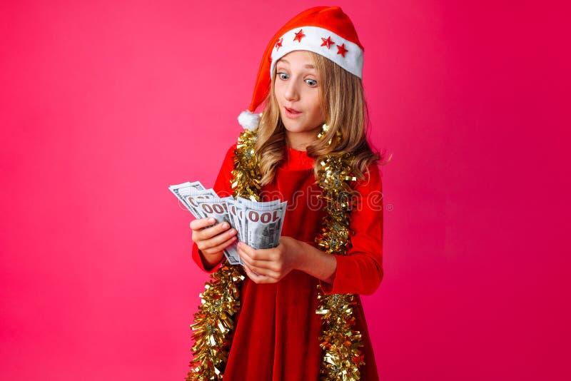 Bära för tonårs- flicka jultomten hatt och glitter runt om hennes hals, H royaltyfri foto