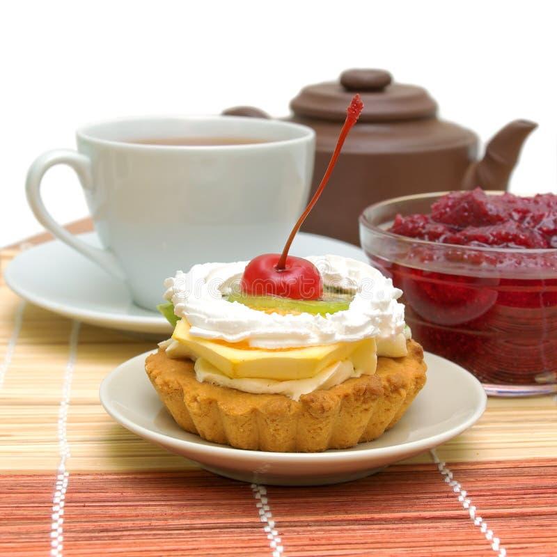 Bära fruktt tårtan mot en kupa av tea och driftstopp royaltyfri bild