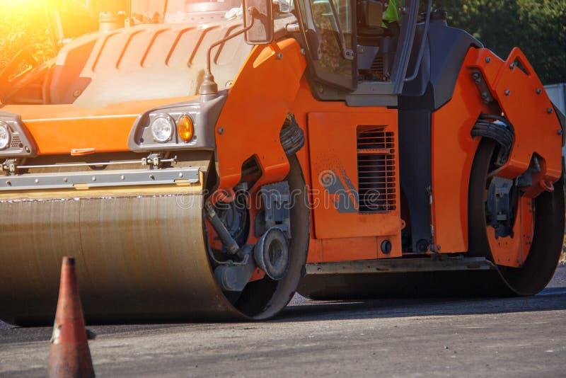Bära ut reparationsarbeten: asfaltera rullen som staplar, och trängande varma lägger av asfalt Maskin som reparerar vägen fotografering för bildbyråer