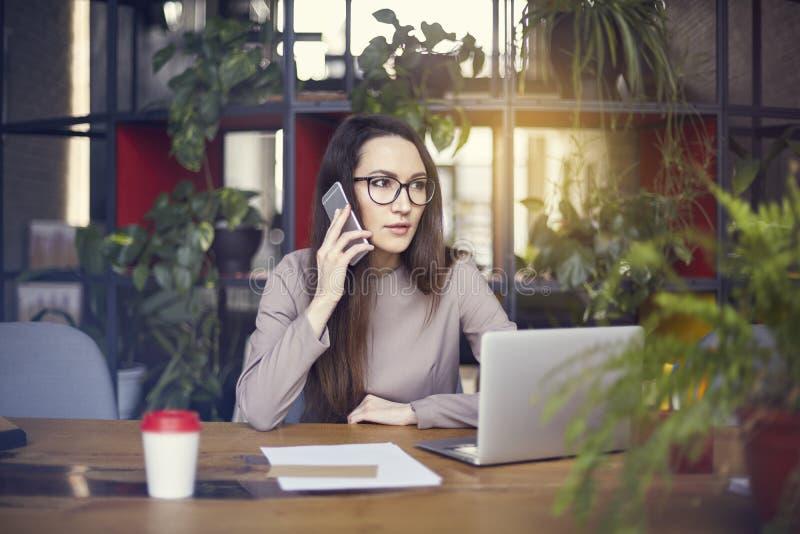Bärande ögonexponeringsglas för härlig flicka i den coworking studion som talar vid smartphonen Begrepp av ungdomarsom arbetar me royaltyfri foto