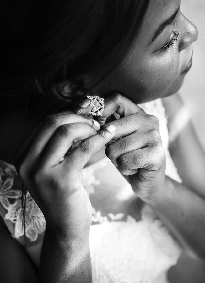 Bärande örhänge för brud på förberedelse för bröllopceremoni fotografering för bildbyråer