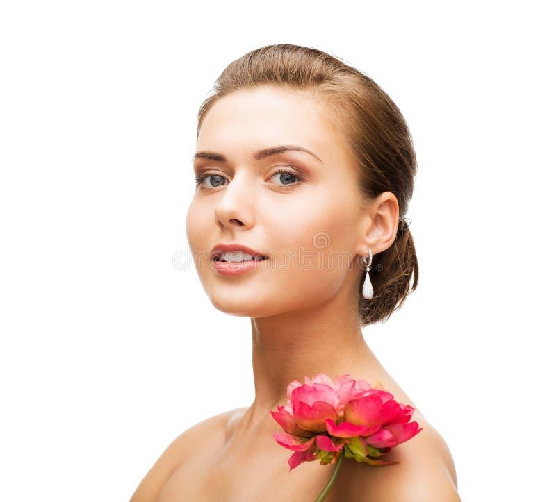 Bärande örhängen för kvinna med blomman royaltyfri bild