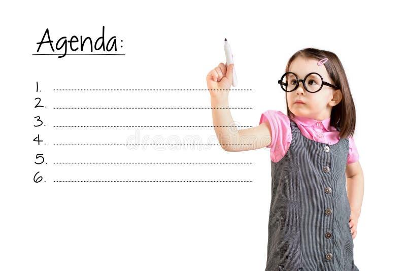 Bärande affärsklänning för gullig liten flicka och skriva tom bakgrund för dagordninglistavit arkivbild