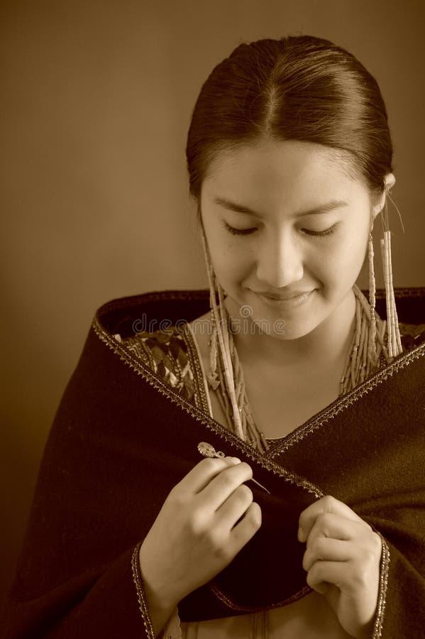Bärande andean traditionella kläder för härlig latinamerikansk modell, mörk poncho överst som ler att posera för kamera medan arkivbilder