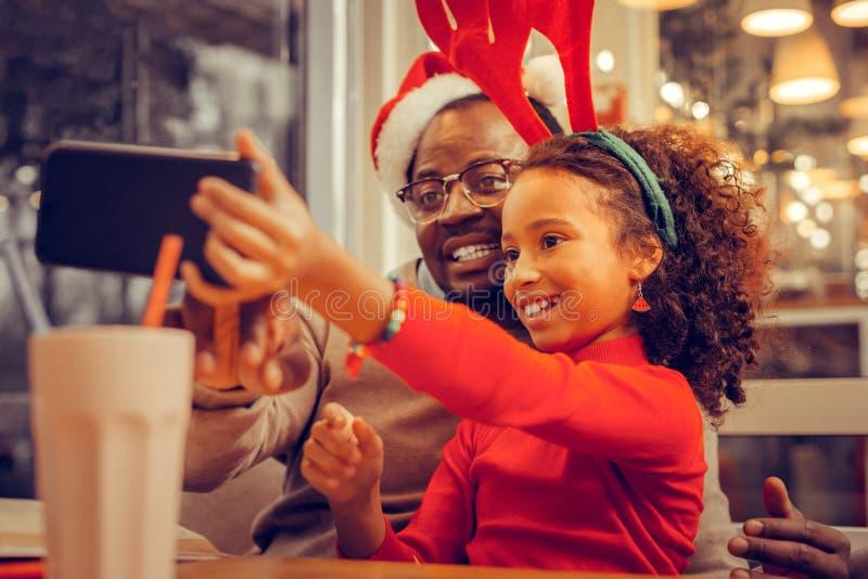 Bärande armband för svartögd flicka som gör selfie med fadern royaltyfria foton