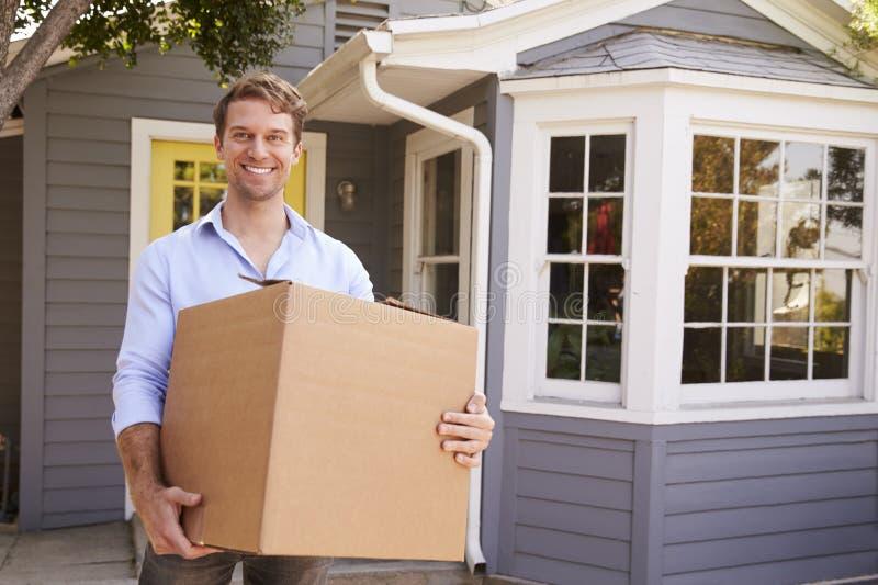 Bärande ask för man in i nytt hem på rörande dag royaltyfri foto