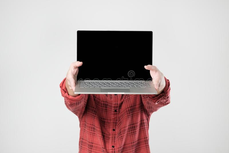 Bärande bärbar dator för man och uppvisningsskärm av den som står dölja hans framsida royaltyfria foton