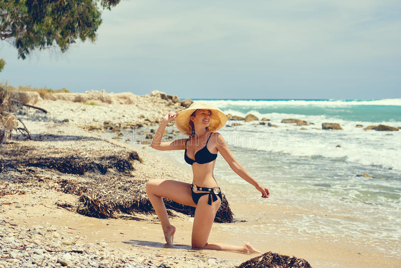 Bärande baddräkt för kvinna som poserar på stranden royaltyfria bilder