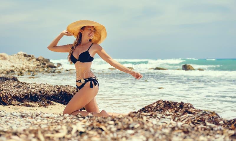 Bärande baddräkt för kvinna som poserar på stranden fotografering för bildbyråer