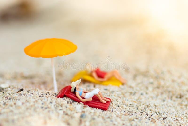 Bärande baddräkt för miniatyrkvinna som kopplar av på stranden på havet Bildbruk för loppaffärsidé royaltyfria bilder