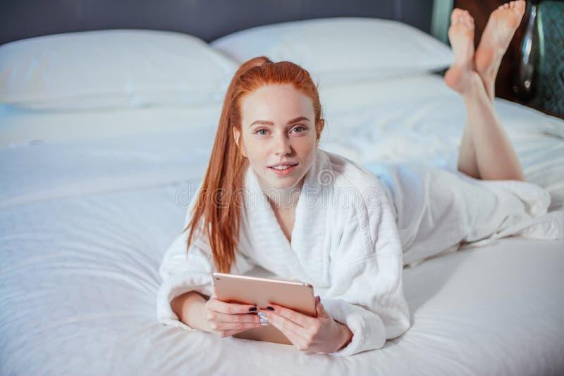 Bärande badrock för härlig kvinna och använda den digitala minnestavlan, medan koppla av på säng royaltyfria foton