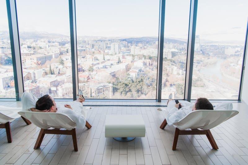 Bärande badrock för ung man som två ligger på dagdrivare i brunnsortsalong och till varandra talar framme av ett stort fönster me royaltyfri foto