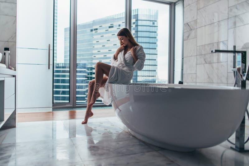 Bärande badrocksammanträde för nätt slank kvinna på kanten av badkarpåfyllning med vatten arkivbild