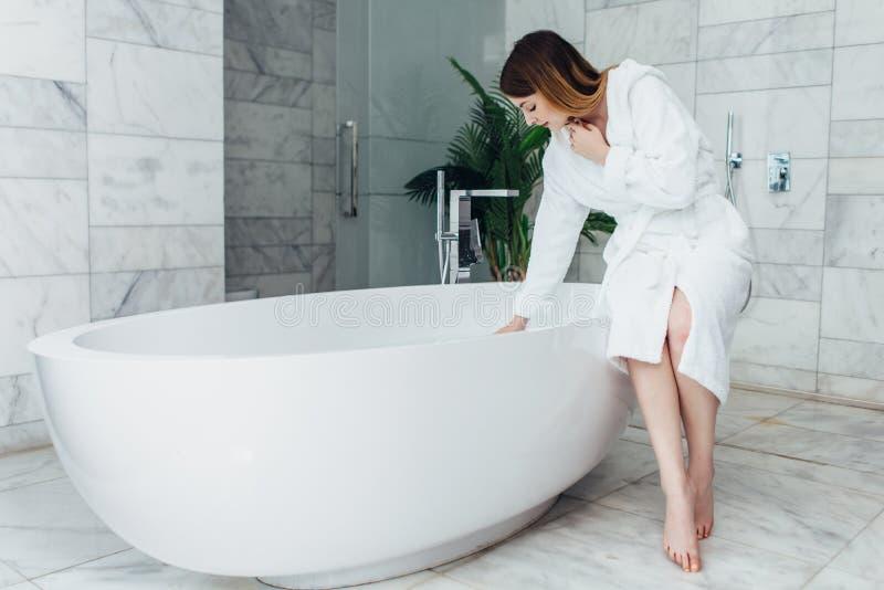 Bärande badrocksammanträde för nätt slank kvinna på kanten av badkarpåfyllning med vatten fotografering för bildbyråer
