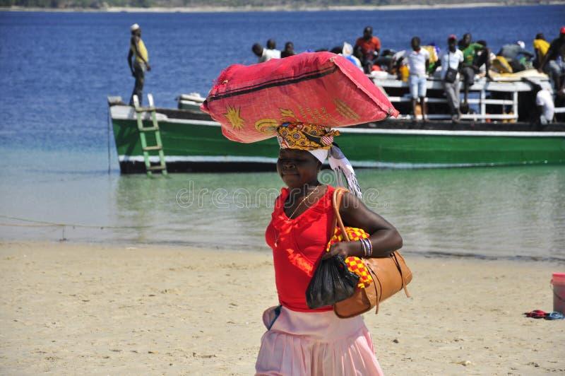 Bärande bagage för afrikansk kvinna på huvudet royaltyfri foto
