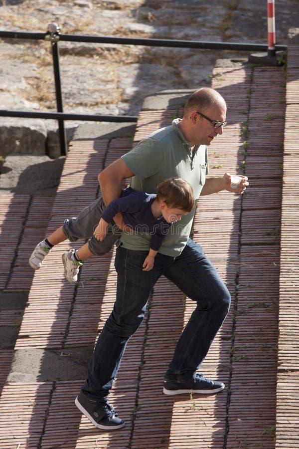 Bärande barn för förälder under hans arm Plast- koppkaffe arkivfoto