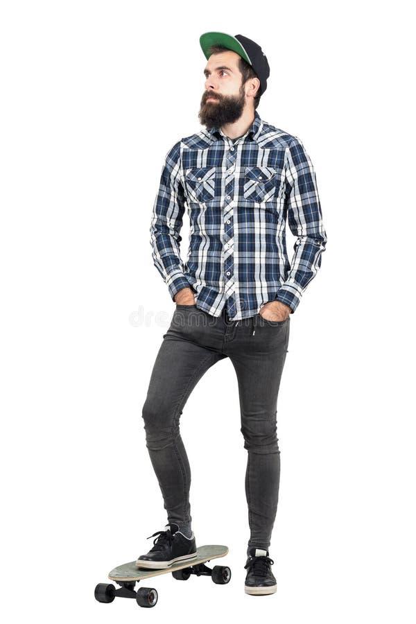 Bärande baseballmössaanseende för säker skäggig hipster på skridskobräde med händer i fack arkivbilder