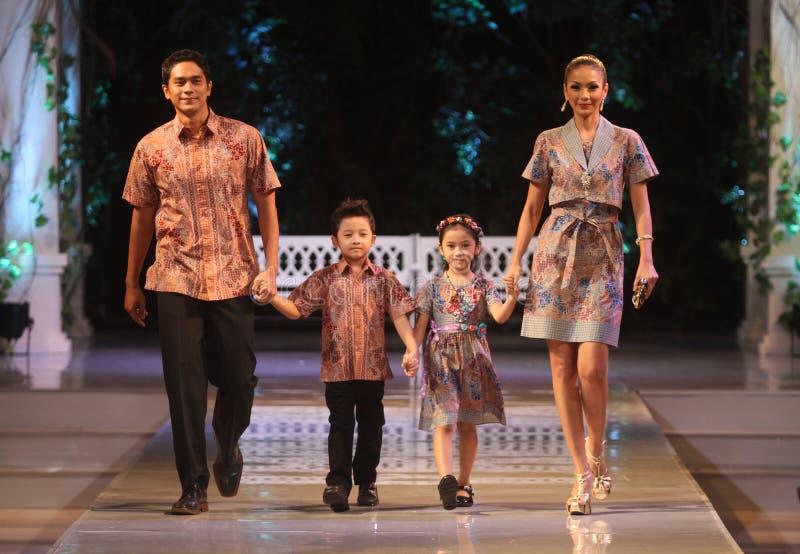 Bärande batik för asiatisk familjmodell på modeshow r royaltyfria bilder