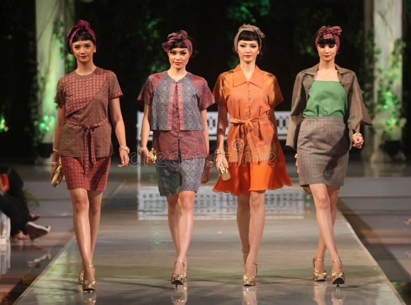 Bärande batik för asiatisk kvinnlig modell på modeshowlandningsbanan royaltyfri bild