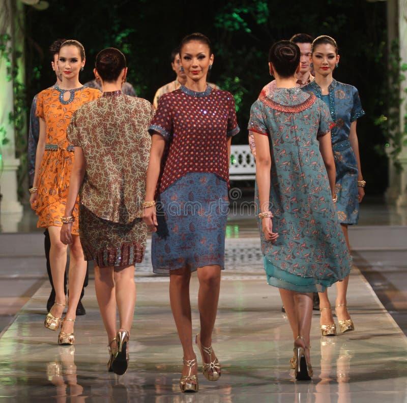 Bärande batik för asiatisk kvinnlig modell på modeshowlandningsbanan arkivfoto