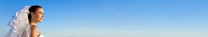 Bärande bröllopsklänning för panorama- rengöringsdukbanerbrud med blå himmel fotografering för bildbyråer