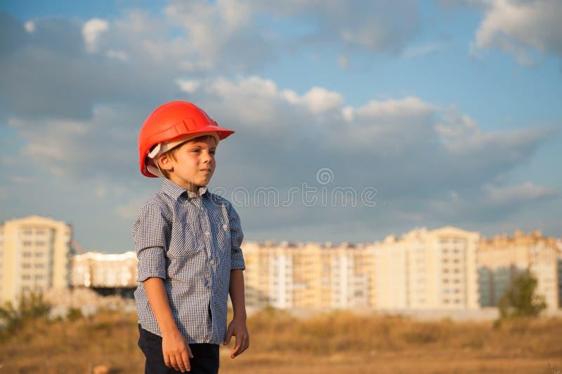 Bärande byggmästarehjälm för gullig unge på nybyggebakgrunden arkivfoton