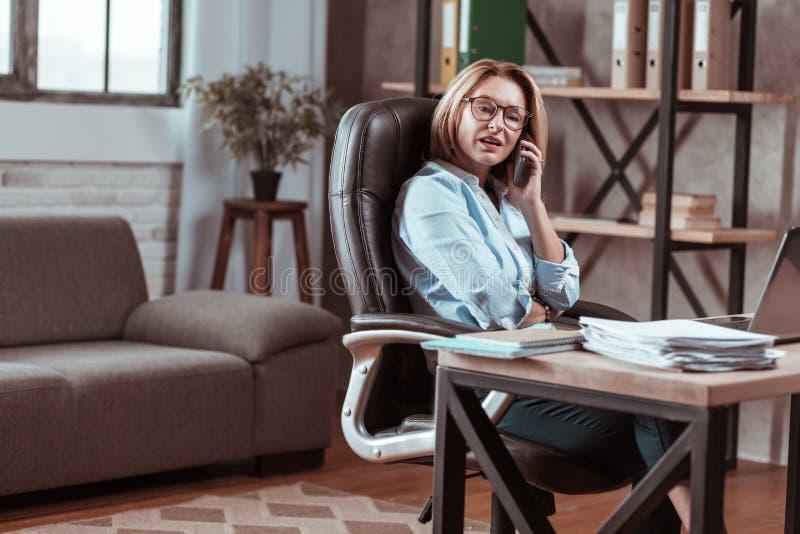 Bärande byxa och blus för kvinna som talar vid telefonen arkivfoton