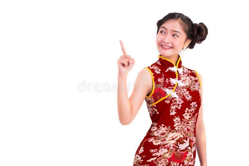 Bärande cheongsam för ung asiatisk skönhetkvinna och peka bredvid G royaltyfri bild