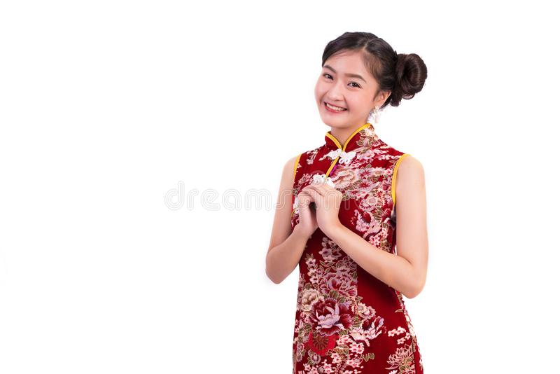 Bärande cheongsam för ung asiatisk skönhetkvinna och välsigna eller hälsa gest i kinesisk festivalhändelse för nytt år på isolera royaltyfri fotografi