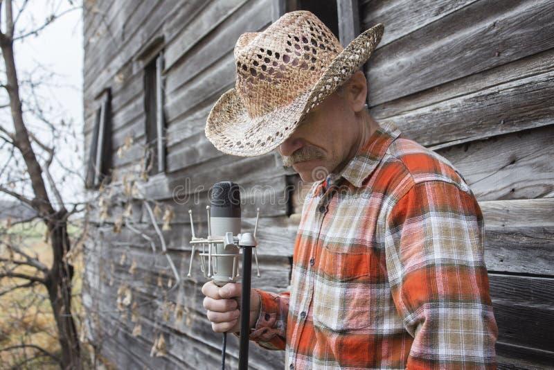 Bärande cowboyhatt för man som rymmer en mikrofon royaltyfri foto