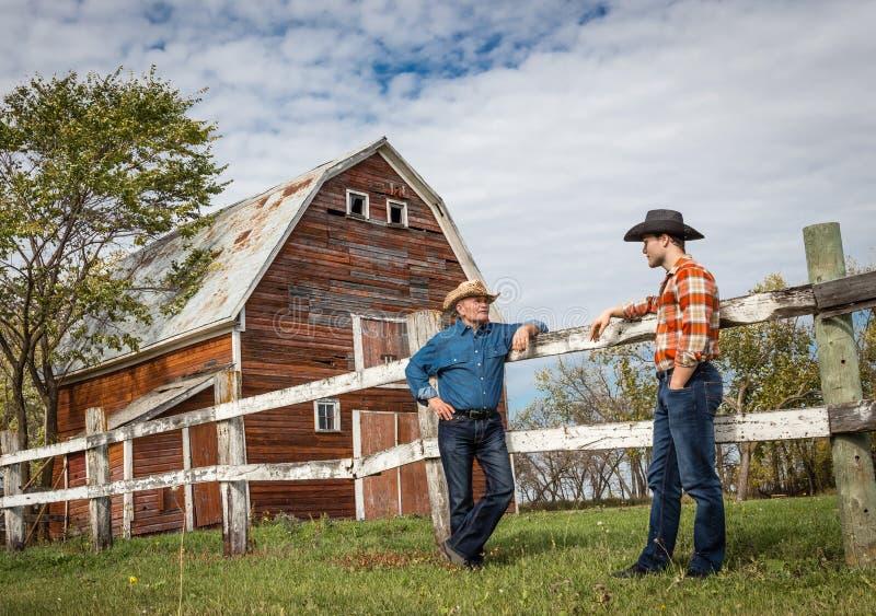 Bärande cowboyhattar för fader som och för fullvuxen son står och pratar vid en röd ladugård arkivbilder