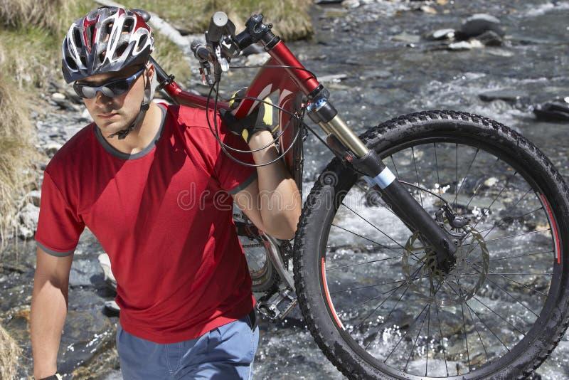 Bärande cykel för cyklist i floden arkivfoto