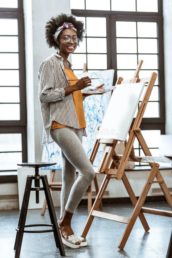 Bärande damasker för slank konstnär som står nära den dra staffli arkivfoton