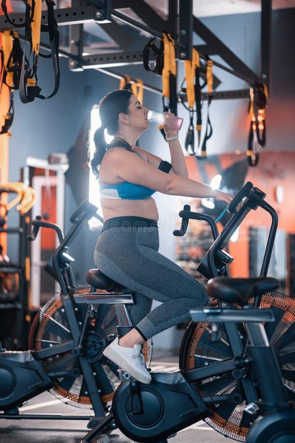 Bärande damasker och överkant för brunett som cyklar i idrottshall royaltyfria bilder