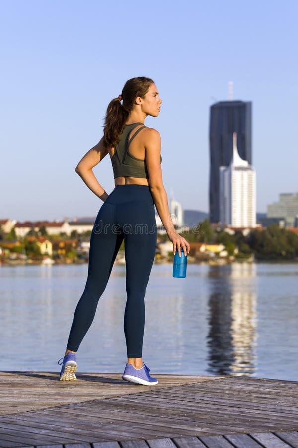 Bärande damasker och gymnastikskor för konditionflicka på en flod arkivfoto