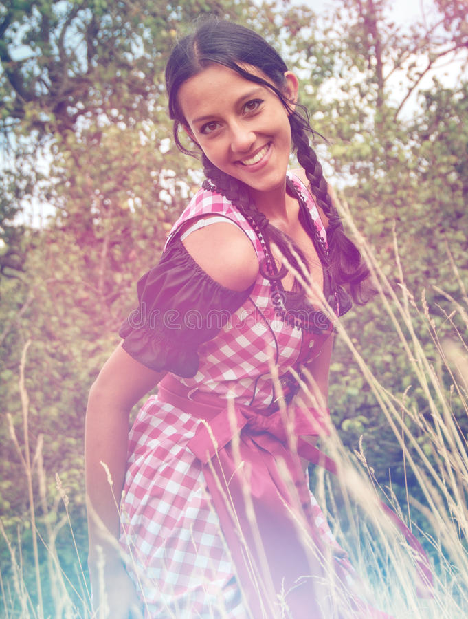 Bärande dirndl för ung kvinna som poserar i fältet arkivfoto