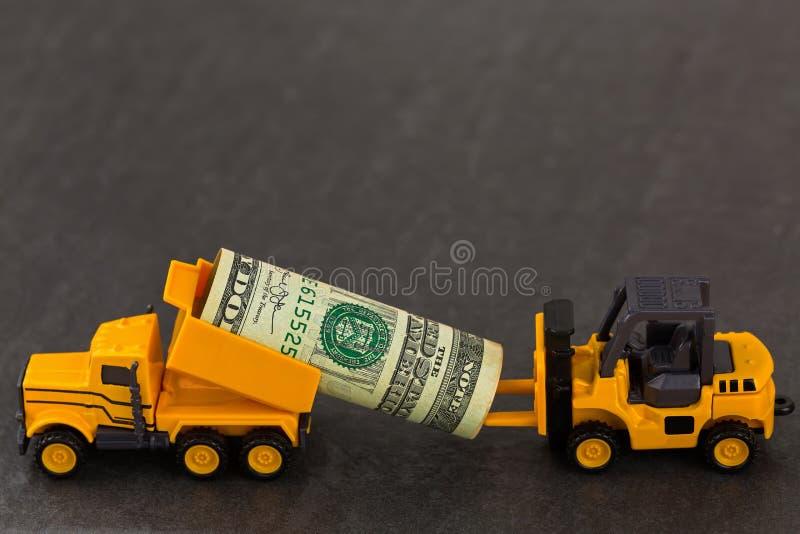 Bärande dollarpengar för gul dumper som överför till gaffeltrucken på b arkivbilder