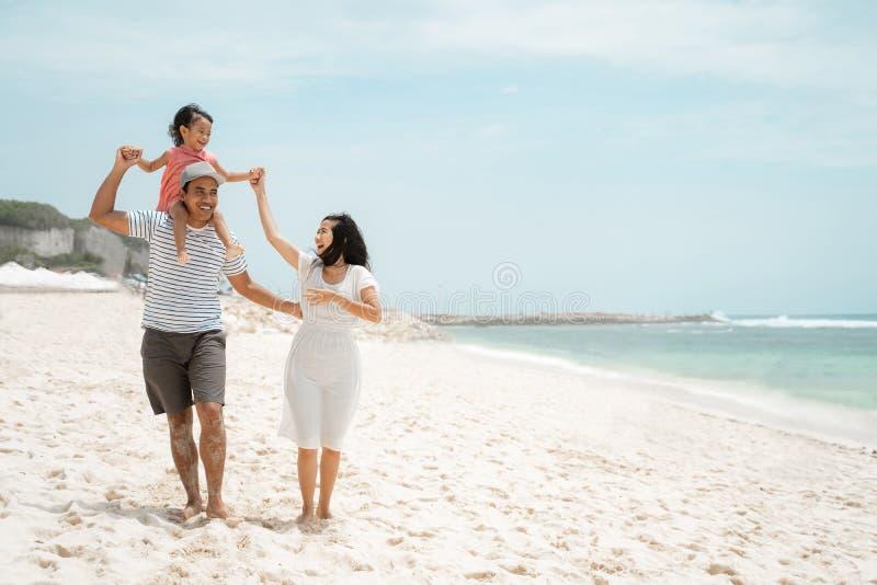 Bärande dotter för ung fader på skuldran, när tyck om stranden med modern royaltyfri foto