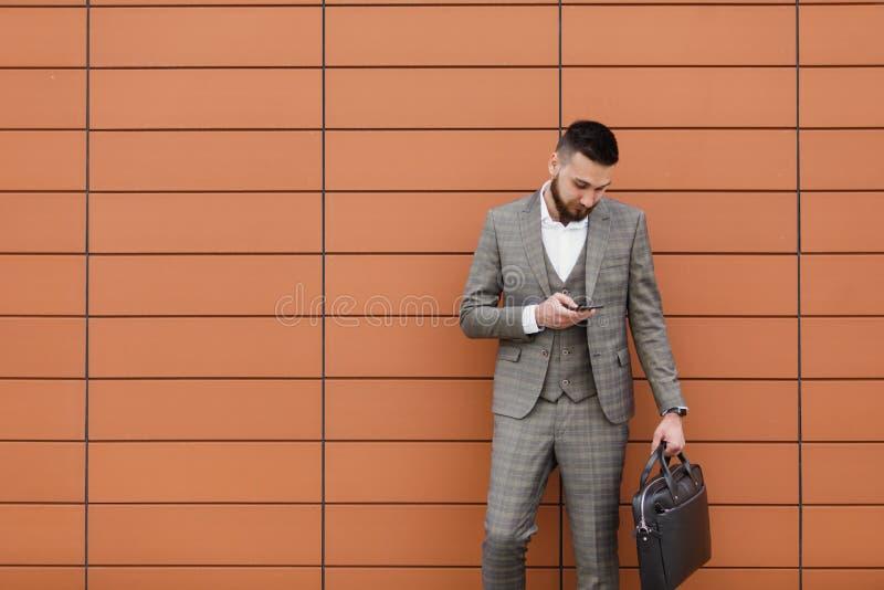 Bärande dräkt för affärsman och använda den moderna smartphonen nära kontoret på ottan, lyckad arbetsgivare för att göra ett avta fotografering för bildbyråer