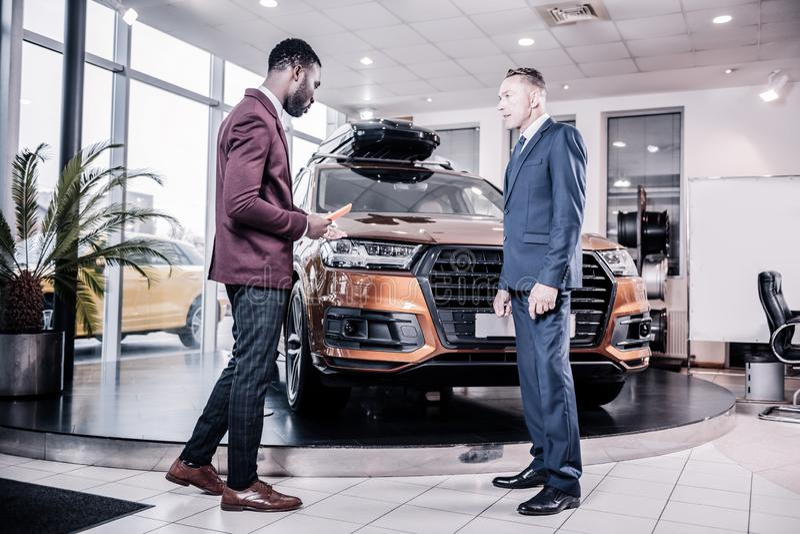 Bärande dräkt för affärsman och svarta skor som köper bilen royaltyfri foto