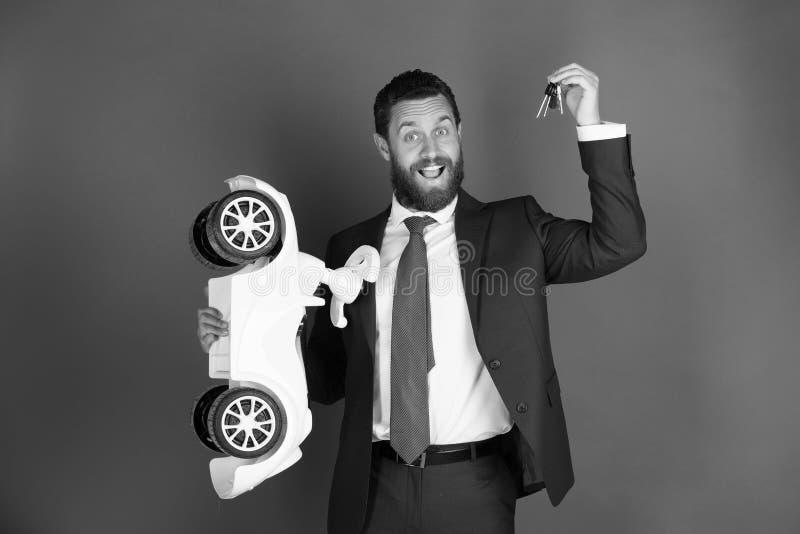 Bärande dräkt för lycklig man med den vita leksakbilen, tangenter royaltyfria foton